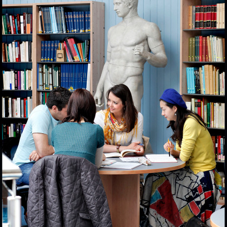 three students sit at a table in the library