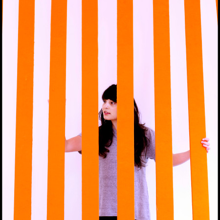 a student stands in front of a display of orange lines