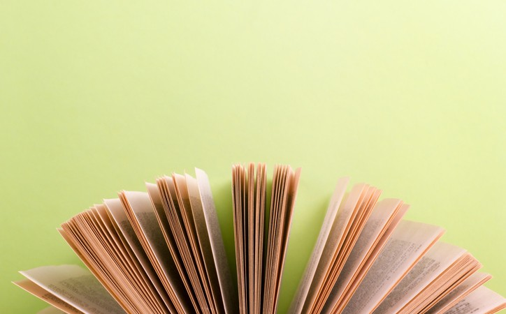 Open hardback book on wooden table and green background