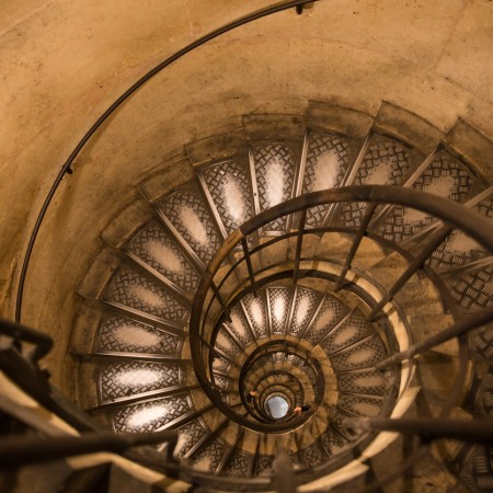 View looking down an elegant spiral staircase with a handrail