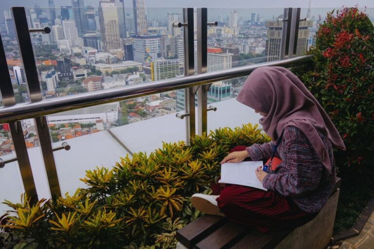 Woman sitting on bench and reading with skyline in background.