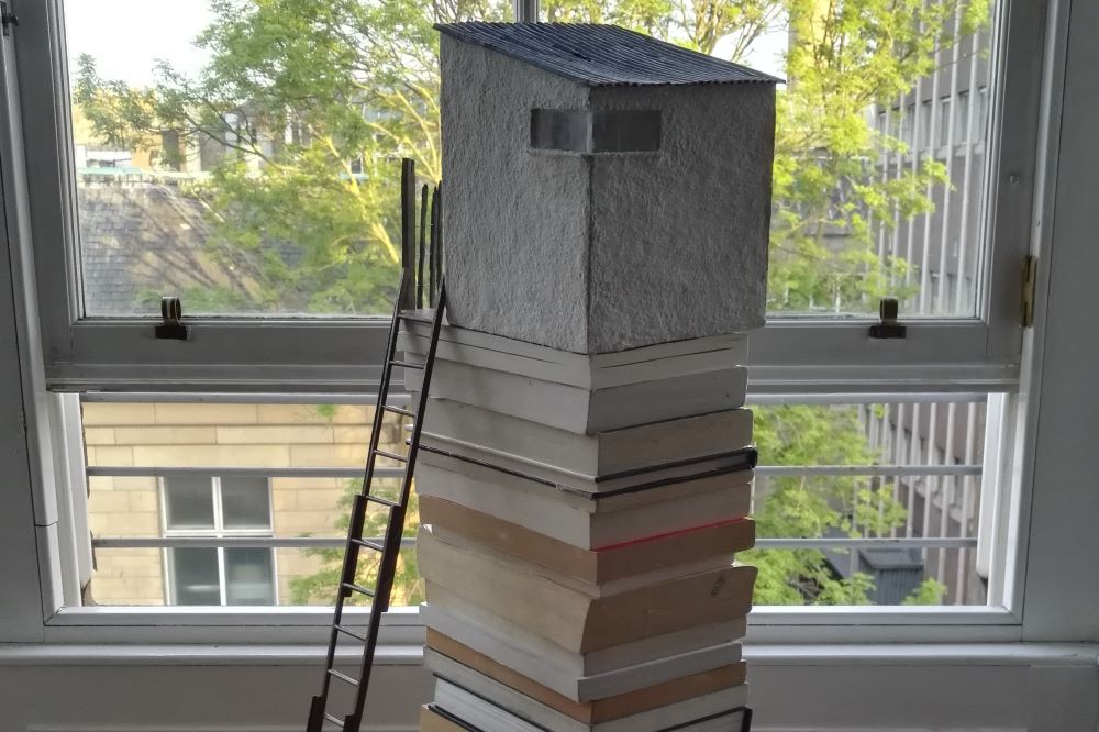Photograph of a sculpture made by the author featuring a model treehouse located on the top of a stack of books with a small model stepladder resting against the house.
