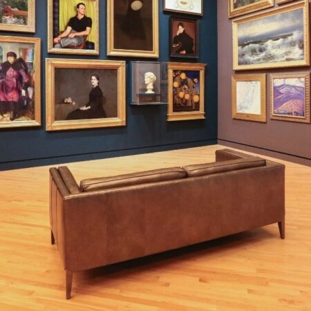 Photograph of a large leather sofa in the middle a room in an art gallery