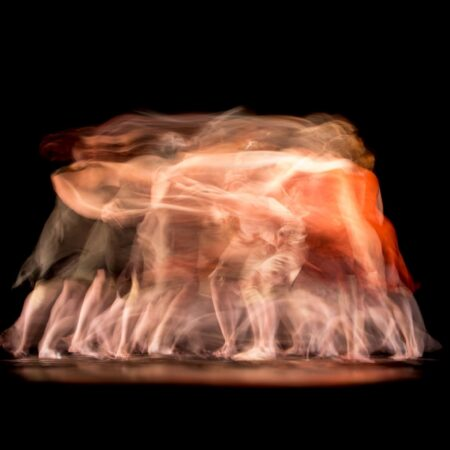 Blurry photo of dancers in black background.