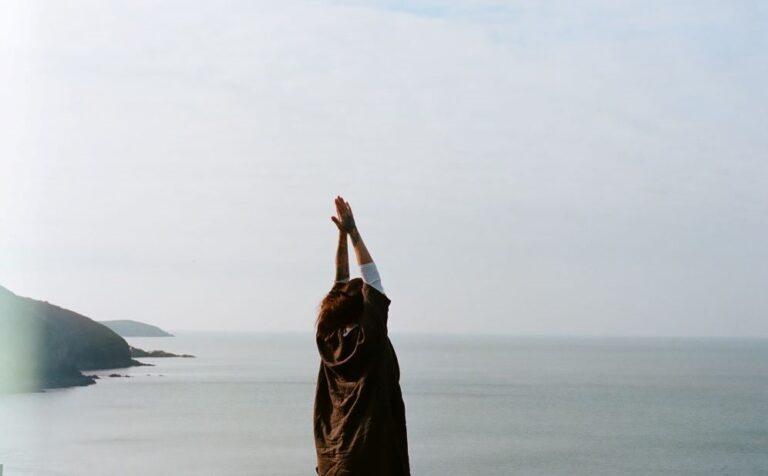 Person doing yoga while facing ocean.