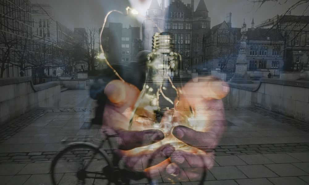 An image of hands offering a lightbulb superimposed onto a photograph of George Square at the University of Edinburgh