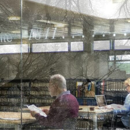 Photograph of two people studying in a research library with the image of tree branches superimposed on the room