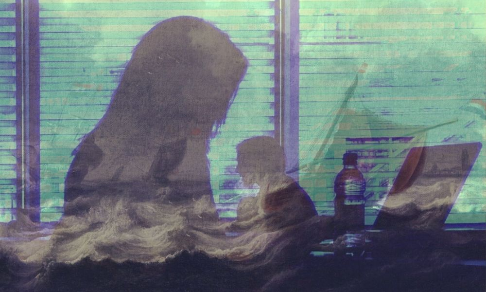 Silhouette of a woman on a laptop with a choppy sea in the background