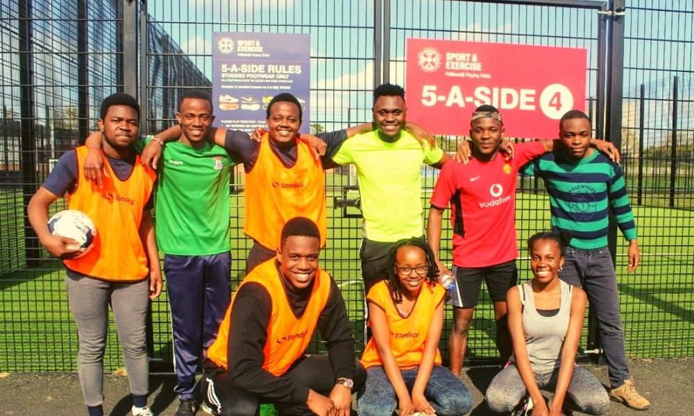 Group photo of football players standing next to an astro turf football pitch