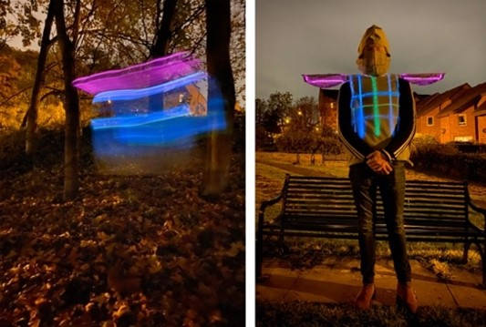 Man standing in front of a bench wearing his wearable artwork which is a rocket-suit with lED lights.