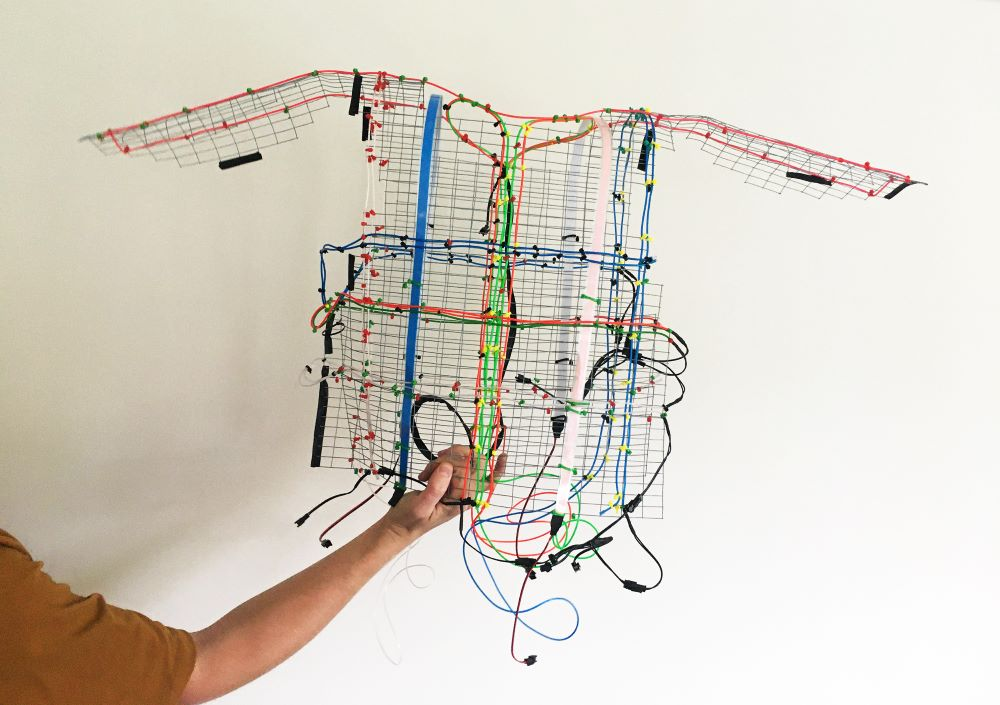 A photograph of a sculpture made out of multi-coloured wires in the shape of a sleeveless shirt being held up by a person's arm.