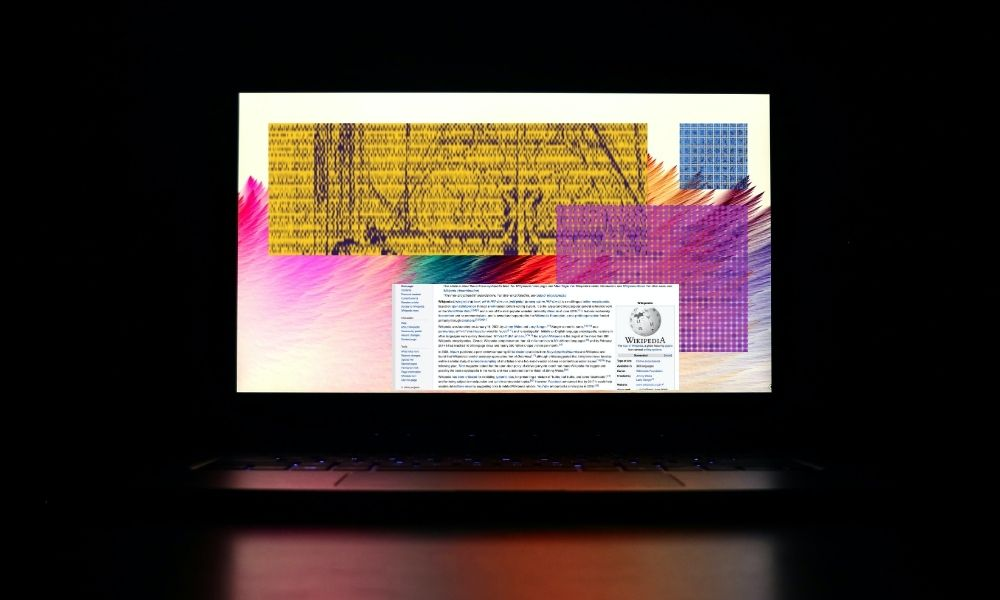 A laptop sitting on a table with four blocks on the screen. One of the blogs is a page from Wikipedia.