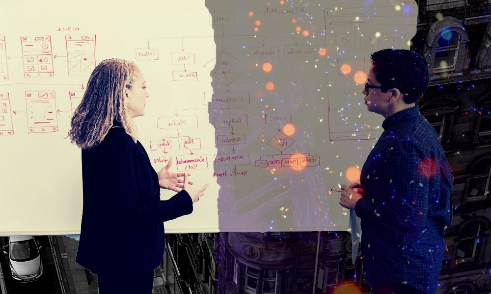 Two women discussing plans on a whiteboard with coloured lights covering half of one of the women.