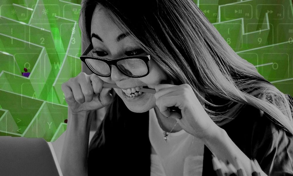 woman biting a pencil looking at a laptop screen with the image of a maze in the background