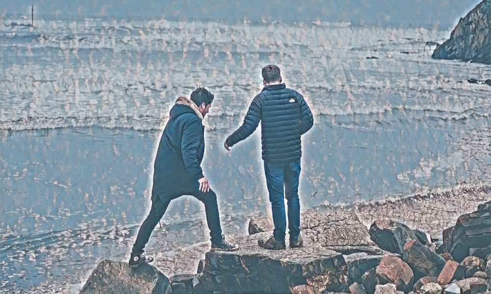 Two men dressed in winter jackets walking across rocks on a beach close to the water on a sunny day